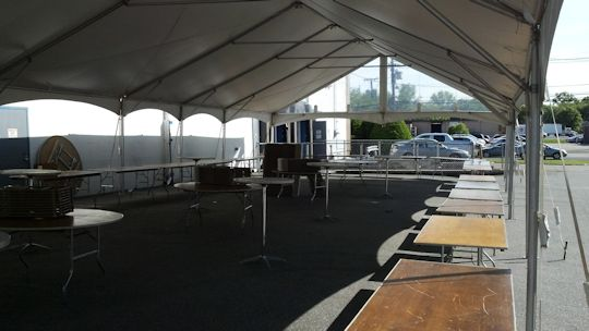 tables set up in a u unter tent