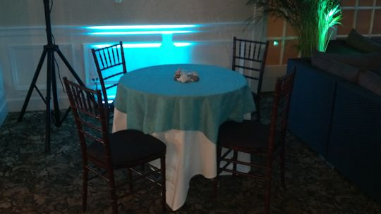 3 foot round tables with turquoise linens and fruitwood chairs